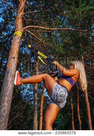 Tough Young Woman In Sports Clothing Doing Fitness In The Forest. Pine Trees And Blue Sky On The Bac
