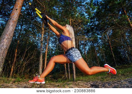 Tough Young Woman In Sports Clothink Doing Fitness In The Forest. Pine Trees And Blue Sky On The Bac