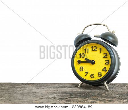 Closeup Alarm Clock Show The Time In A Quarter To Ten O'clock Or 9:45 A.m. On Old Brown Wood Desk Is