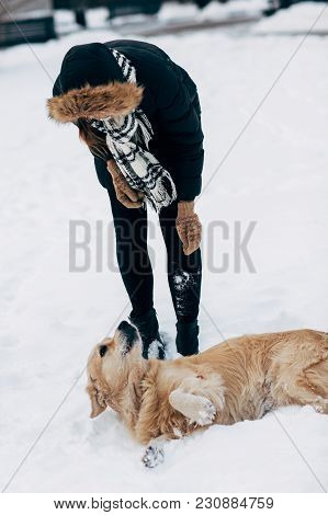 Image Of Girl In Black Jacket With Retriever On Walk In Winter Park At Afternoon.