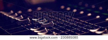 Close-up of sound recording equipment knobs at music studio