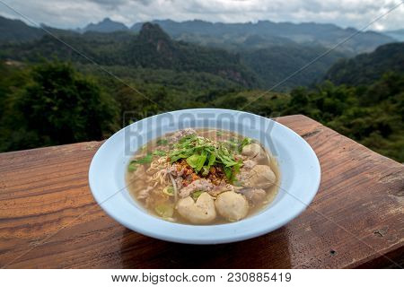 Thai Tom Yum Noodle With Pork And Meatball In A Bowl On The Wooden Table By Mountain View Behind, Tr