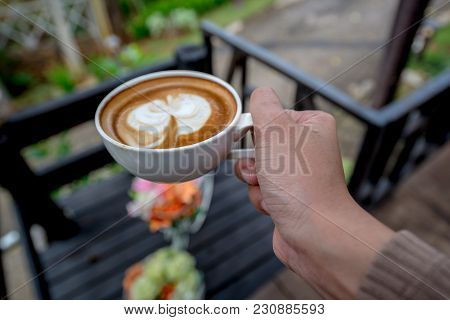Hot Cappuccino Latte Coffee In White Cup Holding By Hand In Front Of A Table