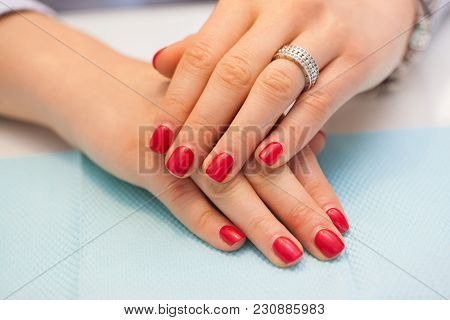 Female Nails With Red Shellac On The Table In Beauty Salon. Beauty And Treatment