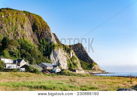 The Eastern Coast Of Northern Ireland With Cliffs, Hills Ahaouses At Antrim Coastal Road, A.k.a. Cau