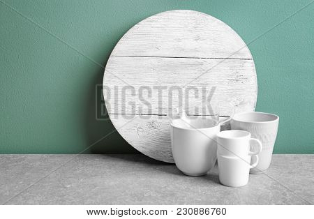 Wooden board and cups on table. Cooking utensils