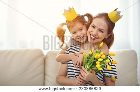 Happy Mother's Day! Mother And Child Daughter In Crowns And With Flowers .