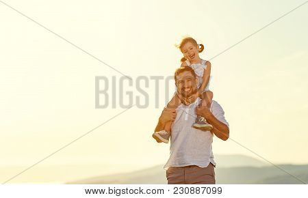Father's Day. Child Daughter Sits On Her Dad Shoulders Outdoors On A Summer .
