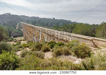 The Ferreres Aqueduct Profile View With Tourist Walking