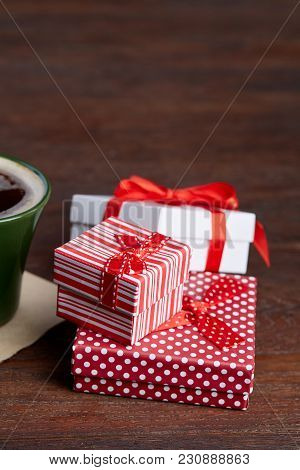 Still Life With Holiday Gift In Small Red Color Box With Pattern, Covered With Red Ribbon And Bow On