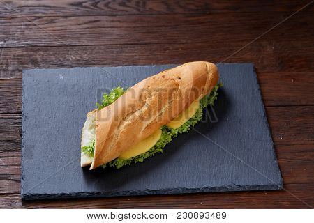 Fresh And Tasty Submarine Sandwich With Cheese And Vegetables On Cutting Board Over Wooden Backgroun