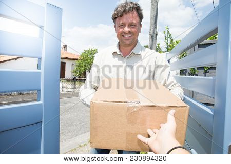 Delivery Man At Home For Signature For Package Delivery To Recipient A Courier Service Concept