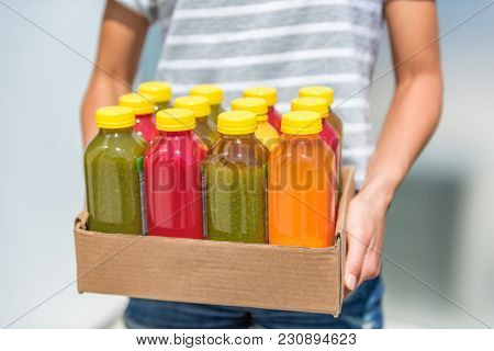 Bottles of juice with fruits and vegetables in delivery box. Cold pressed juicing bottles. Healthy juices for detox.