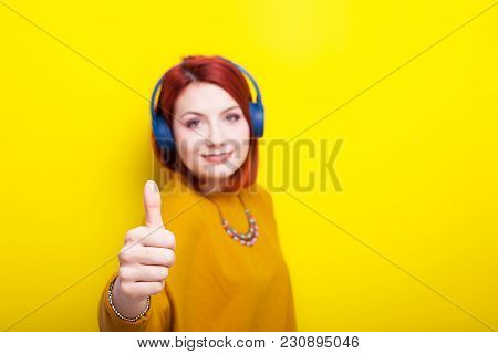 Smilng Woman Looking At The Camera And Raising Her Thumb Up On Yellow Background