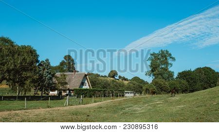 Country House With Thatched Roof, Green Garden And Lawn In Normandy, France On A Sunny Day. Beautifu