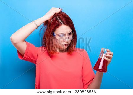 Confused Beautiful Nerd Girl With A Tube Of Red Liquid In Her Hands On Blue Background