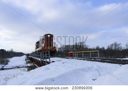 Shunting Locomotive To Ride On The Railway Bridge In Winter. The Locomotive Is Moving Along The Snow