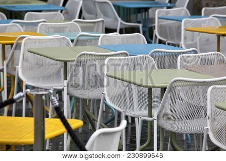 The Restaurant Zone With Colorful Plastic Chairs And Blue, Yellow, White Tables In The Lobby Of The