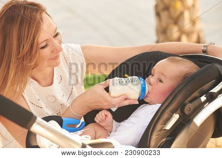 Mother Feeding Her Little Baby From The Bottle