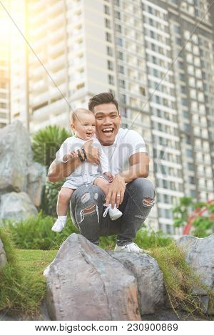 Happy Excited Young Vietnamese Man Playing Outdoor With His Baby