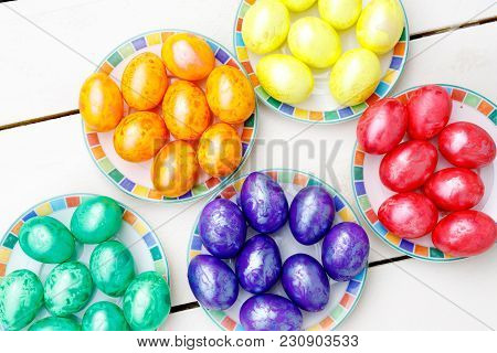Easter Eggs On Wooden Background. Colorful Eggs In Different Colors - Red, Yellow, Orange, Purple An