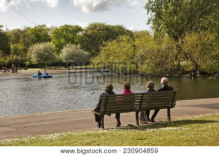 London, England - July 12, 2016 Four Pensioners Sit On A Bench, Admiring The Lake In Victoria Park.