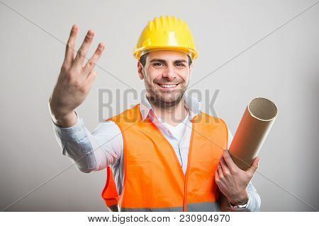 Portrait Of Young Architect Holding Blueprints Showing Number Three