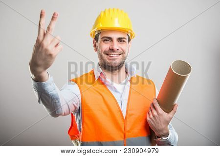 Portrait Of Young Architect Holding Blueprints Showing Number Two