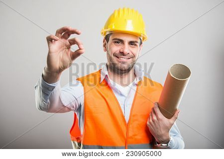 Portrait Of Young Architect Holding Blueprints Making Okay Gesture