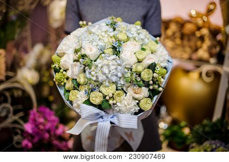 Woman Holding A Beautiful Bouquet Consisting Of Green Ranunculus, White Peonies And Other Tender Flo