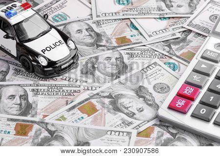 Close-up Of A Police Car Model With Calculator On Dollar Notes. Business And Insurance Concept