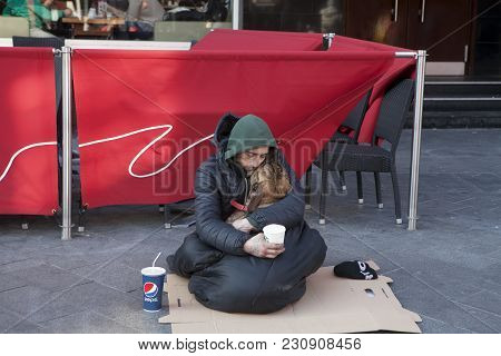 London, England - July 12, 2016 A Beggar Asleep And Holding A Dog In His Arms