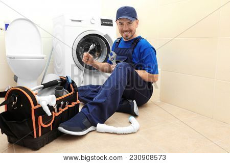 Plumber with set of tools working in bathroom