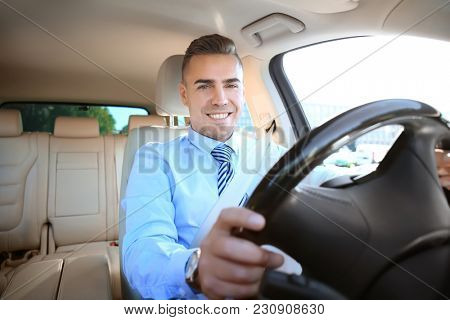 Man in formal wear on driver's seat of car
