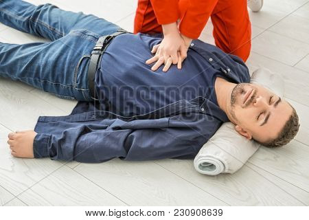Young woman giving first aid to unconscious man on floor, indoors