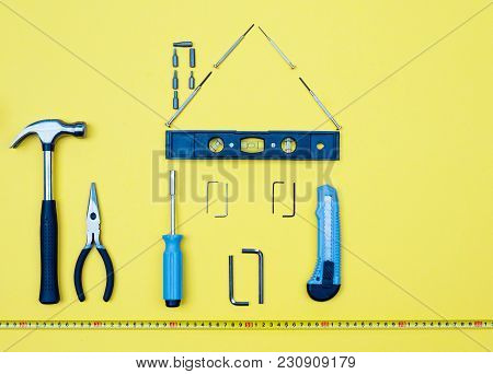 Selection Of Tools In The Shape Of A House Home Improvement Concept On Yellow Background.