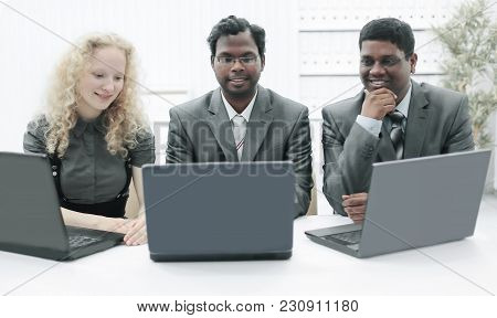 Three Employees Sitting On The Workplace In The Office