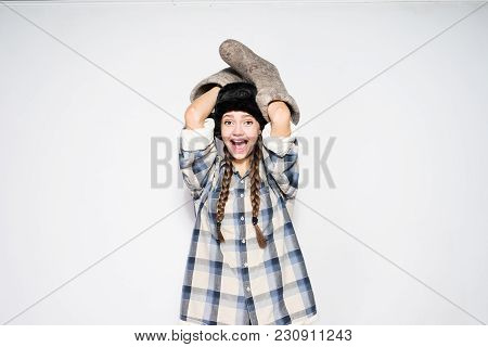 Young Funny Russian Girl In A Warm Fur Hat Holds Winter Boots In Her Hands