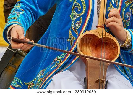 Playing A Musical Instrument Kobyz. The Kobyz Or Qıl-kobız Is An Ancient Kazakh String Instrument. I