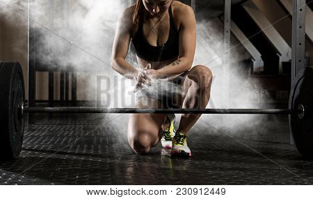 Woman clapping hands and preparing for workout at a gym