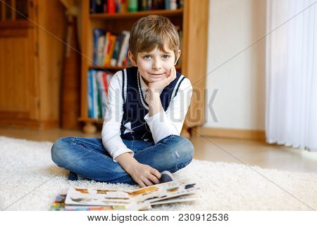 Cute Blond Little Kid Boy Reading Magazine In Domestic Room. Excited Child Reading Loud. Schoolkid,