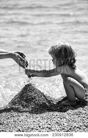 Cute Baby Boy Child With Curly Blond Hair Sit On Beach And Plays With Pebble On Blue Sea Background