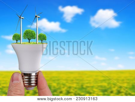 LED bulb with wind turbines in hand. Green energy concept.