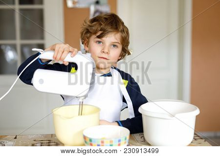 Beautiful Funny Blond Little Kid Boy Baking Chocolate Cake And Tasting Dough In Domestic Kitchen. Ha
