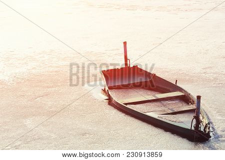 Frozen Into Ice Of River, Lake, Pond Old Wooden Boat. Abandoned Rowing Fishing Boat In Winter River.