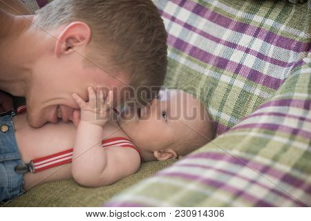 Child Care, Cuddling, Babysitting. Father Play With Baby Son On Sofa. Man With Newborn Kid In Jeans