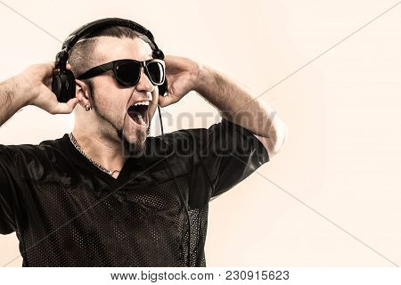 Creative Rapper In The Headphones And Dark Glasses Performs A Rap Song .photo On A White Background