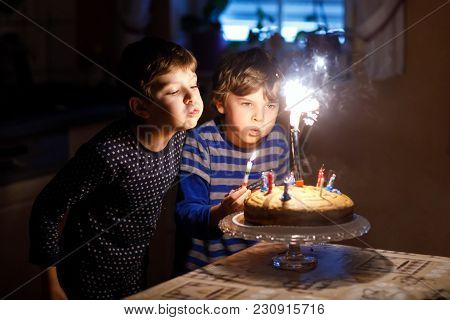 Two Beautiful Kids, Little Preschool Boys Celebrating Birthday And Blowing Candles On Homemade Baked