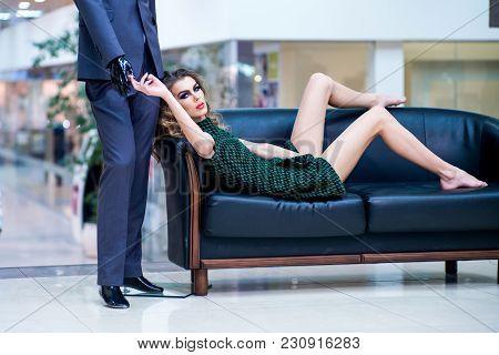 Shop, Shopping, Sale. Woman Shopper Relax On Sofa With Fashion Mannequin In Shop. Girl Shopaholic Ti