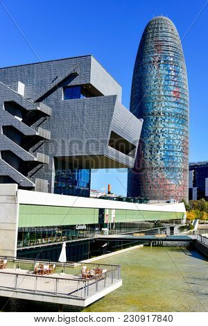 BARCELONA, SPAIN â?? MARCH 8, 2018: The Disseny Hub Barcelona museum and the Torre Glories, formerly known as Torre Agbar, designed by the famous architect Jean Nouvel, in the background